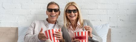 Laughing couple in 3d glasses holding buckets with popcorn on bed, panoramic shot