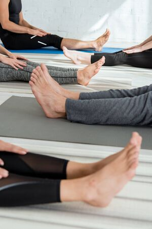 cropped view of barefoot people sitting on yoga mats in staff pose