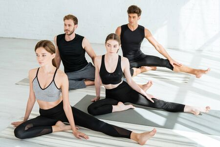 young people in sportswear practicing yoga in half pigeon pose 스톡 콘텐츠