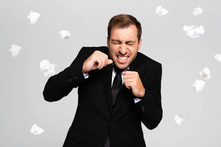 handsome and scared businessman in suit standing near falling crumpled papers isolated on grey Stock fotó