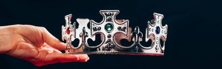 cropped view of woman holding silver crown with gemstones, isolated on black, panoramic shot