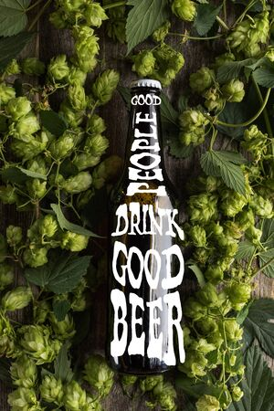 top view of fresh beer in bottle with good people drink good beer lettering in green hop on wooden surface