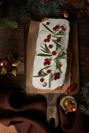 top view of traditional Christmas cake with cranberry near pine and candles on wooden table