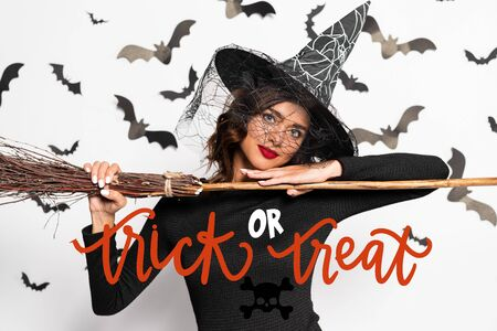 attractive woman in witch hat holding broom in Halloween near trick or treat lettering