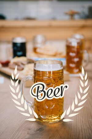 selective focus of mug with lager and beer illustration on wooden table Stock fotó