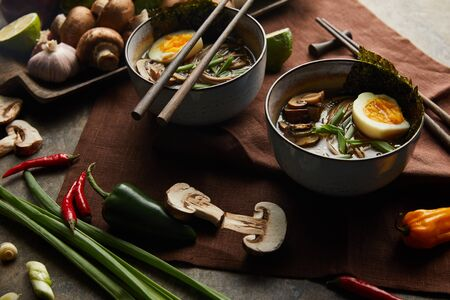 traditional spicy ramen in bowls with chopsticks and vegetables on brown napkin on stone surface Stock Photo