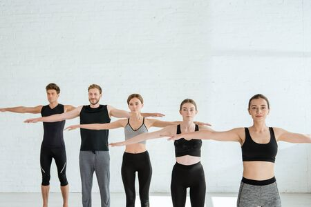 five young men and women practicing yoga in mountain open arm pose 스톡 콘텐츠
