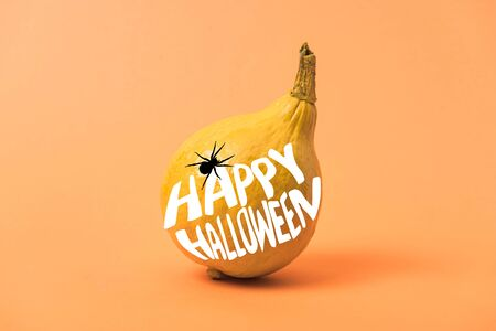 painted yellow Halloween pumpkin on orange colorful background with spider and happy Halloween illustration Stock fotó