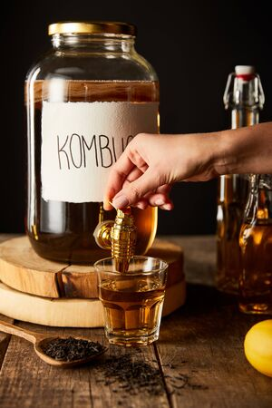 cropped view of woman pouring kombucha in glass from jar on wooden table isolated on black