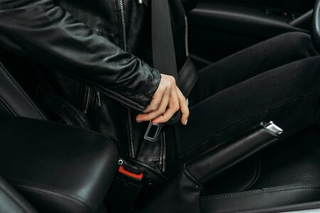 Cropped view of woman fasting safety belt in car
