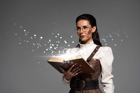 pensive steampunk woman in glasses holding open book with fairy glowing illustration isolated on grey