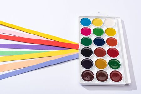 high angle view of watercolor and bright paper strips on white background
