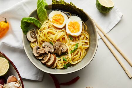 top view of traditional asian ramen in bowl near chopsticks, napkin and vegetables on grey surface Stock Photo