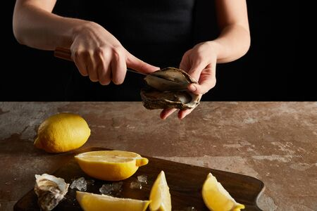 cropped view of woman holding knife while opening oyster near lemons isolated on black