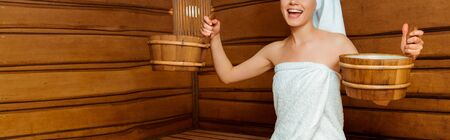 panoramic shot of smiling woman in towels holding washtubs in sauna