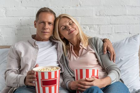 Couple holding popcorn buckets and sitting on bed