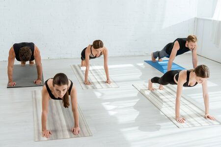 five young people practicing yoga in plank pose