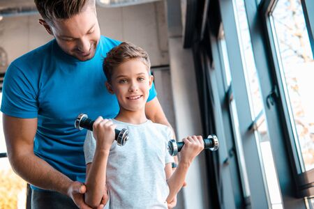 happy father looking at cute son with dumbbells Zdjęcie Seryjne