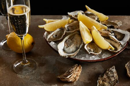 champagne glasses with sparkling wine near oysters and fresh lemons in bowl