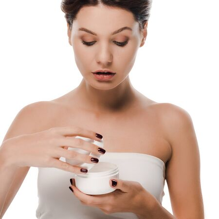young woman looking at container with face cream isolated on white Archivio Fotografico - 134812136