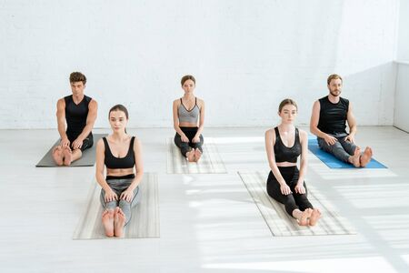five young people practicing yoga in staff pose