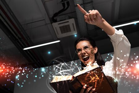 low angle view of angry steampunk woman holding open book with fairy glowing illustration, screaming and pointing with finger