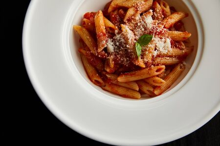 top view of tasty bolognese pasta with tomato sauce and Parmesan in white plate isolated on black