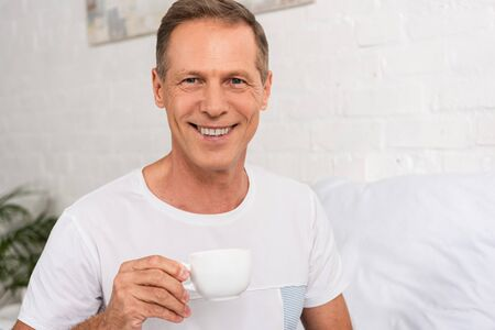 Man holding coffee cup and smiling at camera in bedroom