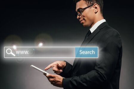 side view of smiling african american businessman using digital tablet on dark background with search bar illustration