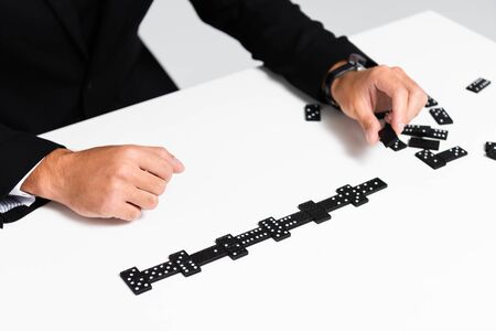 cropped view of businessman in suit playing domino
