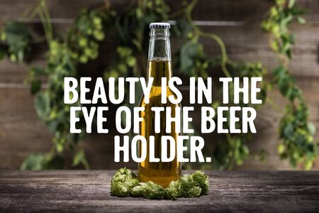 fresh beer in bottle with green hop on wooden surface with beauty is in the eye of the beer holder illustration