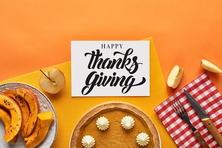 top view of delicious pumpkin pie near card with happy thanksgiving illustration on orange background with apples