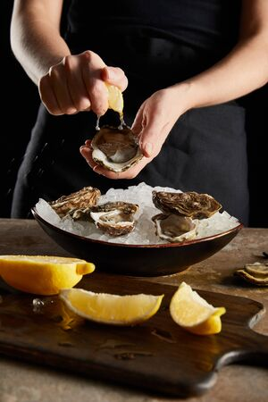 selective focus of woman squeezing lemon on oyster isolated on black