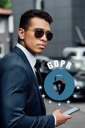 handsome and confident african american businessman in suit and sunglasses using smartphone with gdpr illustration