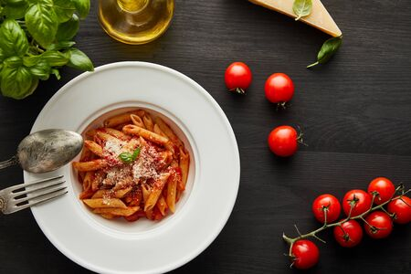 top view of tasty bolognese pasta with tomato sauce and Parmesan in white plate near ingredients and cutlery on black wooden background 写真素材