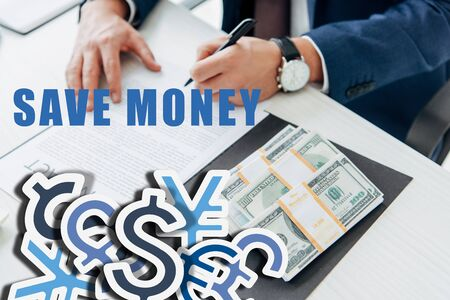 cropped view of businessman signing contract near money in office with save money illustration Stock Photo
