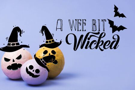 painted festive Halloween pumpkins on violet background with a wee bit wicked illustration