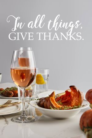 glasses with rose wine, baked pumpkin and carrots served on white marble table isolated on grey with in all things give thanks illustration