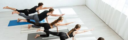 panoramic shot of young people practicing balancing table pose