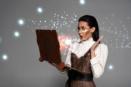 shocked steampunk woman in glasses using vintage laptop with glowing illustration isolated on grey