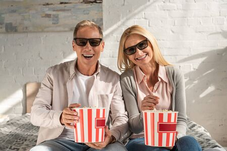 Smiling couple in 3d glasses holding buckets with popcorn on bed