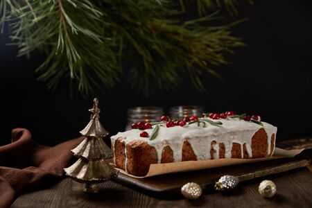 traditional Christmas cake with cranberry near pine, baubles and candles on wooden table