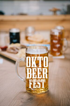selective focus of mug with lager beer and Oktobeerfest illustration on wooden table