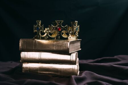 ancient golden crown with gemstones on books on black cloth Imagens - 134812567
