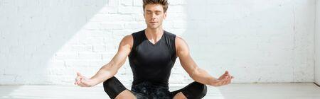 panoramic shot of handsome young man practicing yoga in half lotus pose