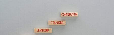 panoramic shot of wooden blocks with leadership, teamwork, contribution words on grey background, business concept