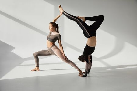 Two girls practicing acroyoga in sunny studio 스톡 콘텐츠