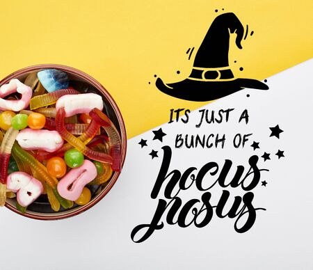 top view of colorful gummy sweets in bowl on yellow and white background with it is just a bunch of hocus pocus illustration 版權商用圖片