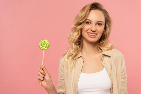 Smiling woman with dental braces holding lollipop isolated on pink