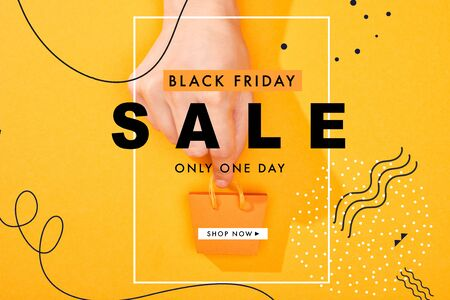 cropped view of hand holding small shopping bag on bright orange background with black Friday sale illustration 版權商用圖片